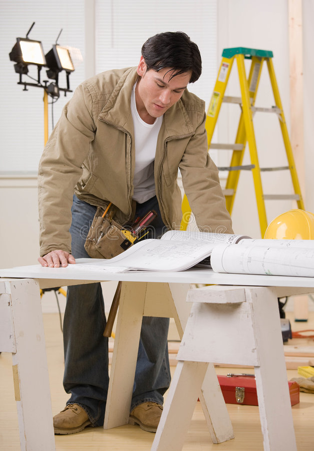 Construction worker looking at blueprints royalty free stock photo