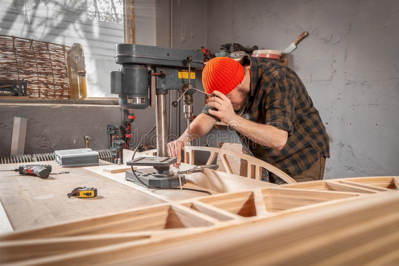 Construction Worker. A man carpenter in a hat and a shirt  is carving a wooden board on a large drilling machine in a workshop side view, in the background a lot stock photography