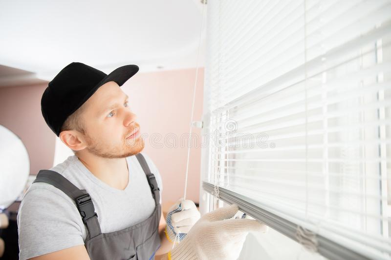 Construction worker man install blinds on plastic white upvc windows in house stock photo