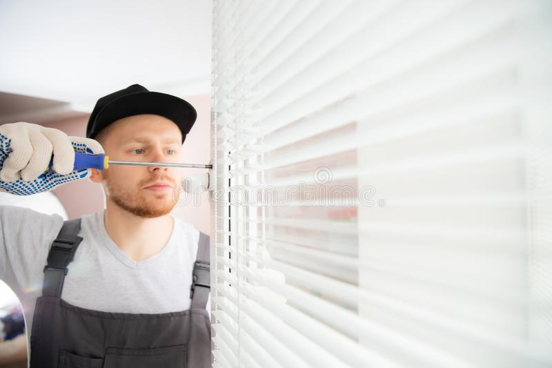 Construction worker man install blinds on plastic white upvc windows in house stock image