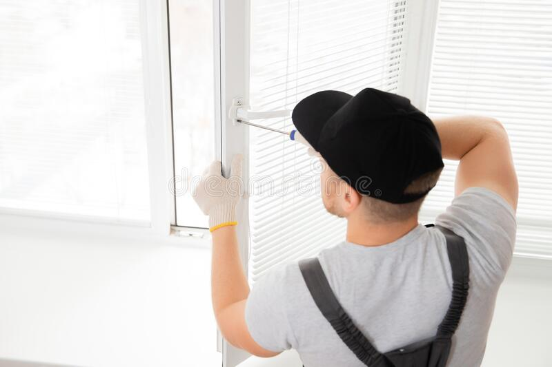 Construction worker man install plastic white upvc windows in house stock photography