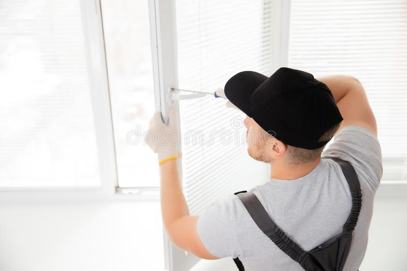 Construction worker man install plastic white upvc windows in house.  royalty free stock photography