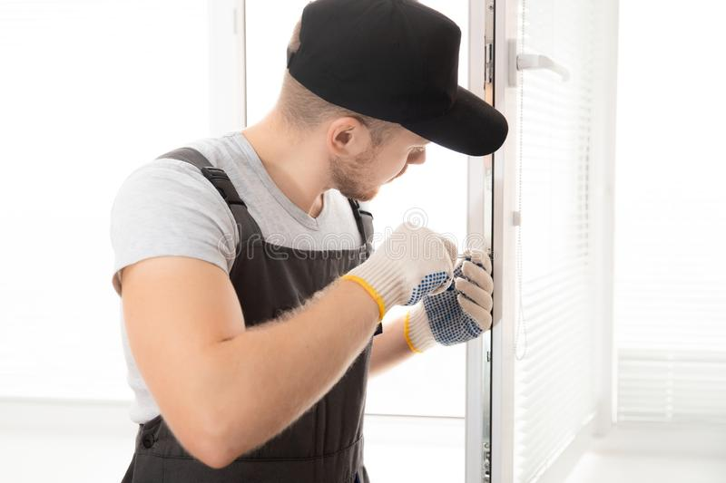 Construction worker man install plastic white upvc windows in house.  stock photography
