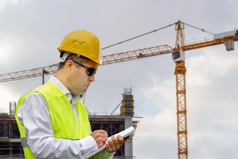 Construction worker man with safety helmet and vest works at construction site. Concept of people working in industrial field royalty free stock images