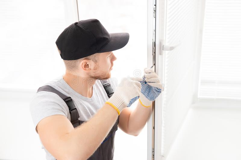 Construction worker man uses screwdriver to screw handle install plastic white upvc windows in house stock photos