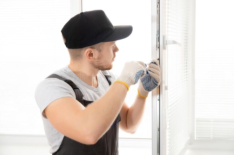 Construction worker man uses screwdriver to screw handle install plastic white upvc windows in house royalty free stock image