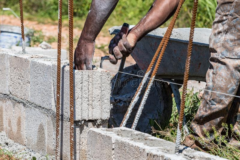 Construction worker/mason/bricklayer laying cement block stock image