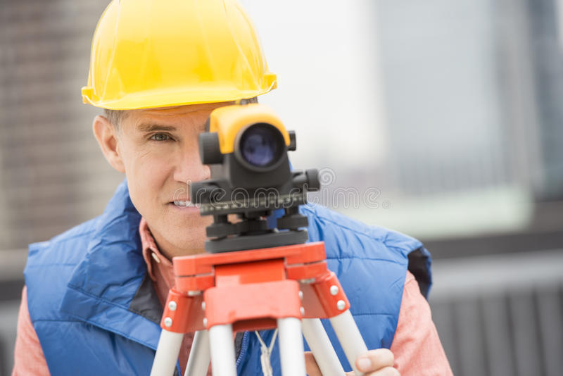 Construction Worker Measuring Distances With Theodolite. Mature construction worker measuring distances with theodolite at construction site royalty free stock images