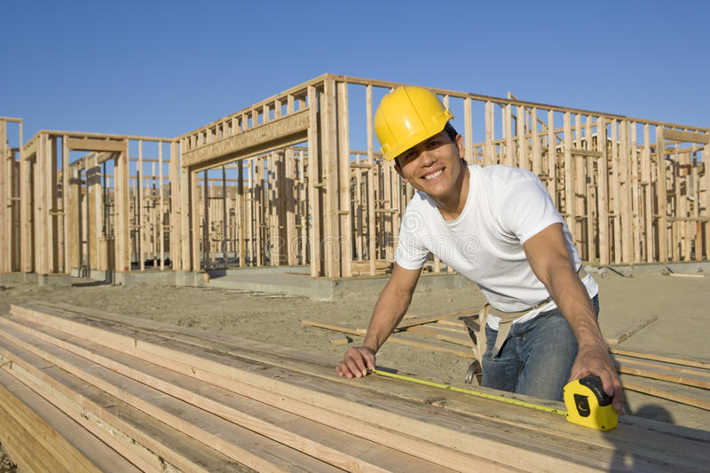 Construction Worker Measuring Planks stock photo