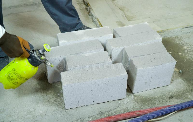 Construction worker moisturing aerated concrete blocks with water sprayer. Male builder in uniform and gloves dampening bricks. house building, construction stock photography