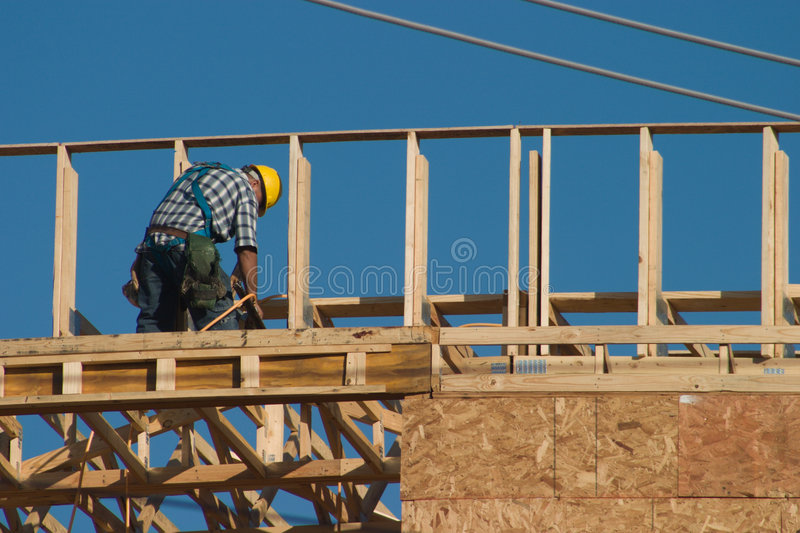 Construction Worker and Nail Gun 2. A lone construction worker on top of a new building with a nail gun strapped to his workbelt. No recognizable faces in image stock photography