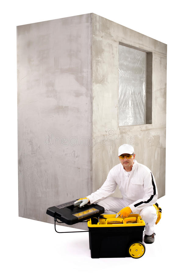 Construction worker with open toolbox and cement wall on white b stock photo