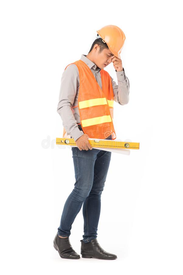 Construction worker in orange waistcoat. Studio portrait of construction worker in orange waistcoat and hardhat holding levelling tool and building plan royalty free stock image