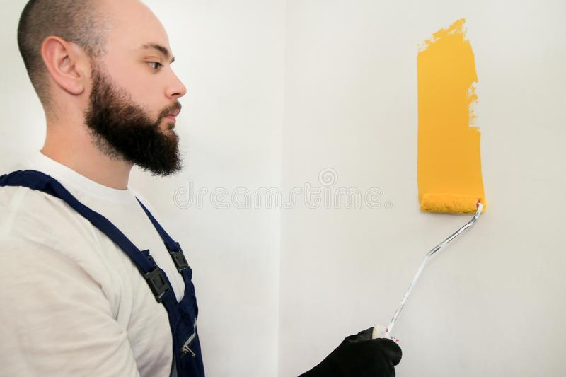 Construction worker and painter using paint roller brush painting of wall with yellow color. royalty free stock image