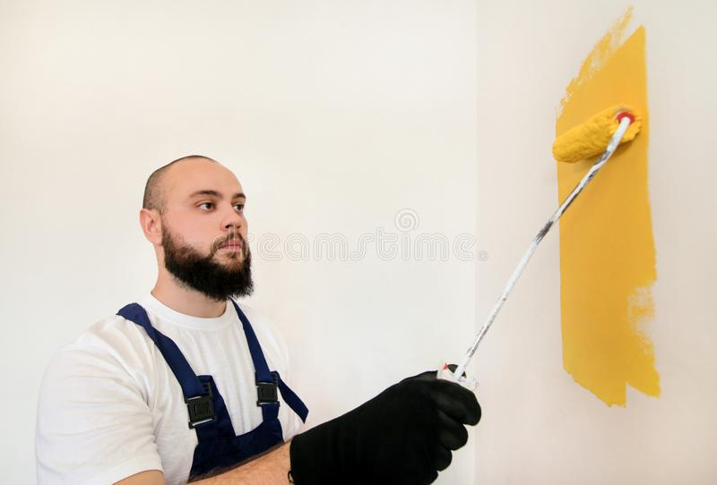 Construction worker and painter using paint roller brush painting of wall with yellow color. stock image