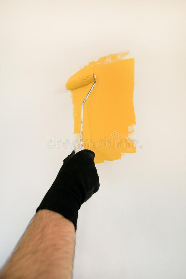 Construction worker and painter using paint roller brush painting of wall with yellow color. royalty free stock photos