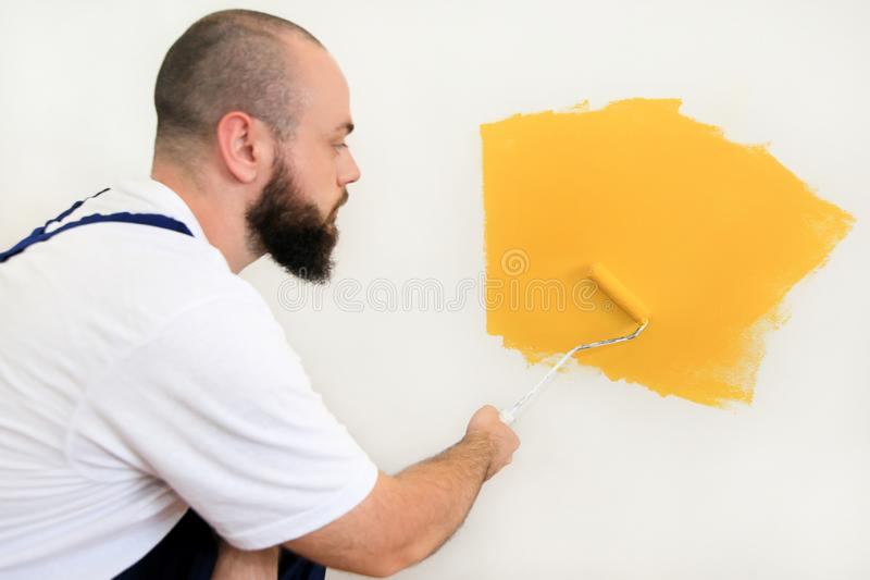 Construction worker and painter using paint roller brush painting of wall with yellow color. stock photography