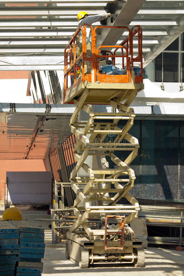 Construction Worker Painting Beam using Lift. Construction worker, using a self-propelled hydraulic scissor lift, painting a beam with a roller. Note the safety stock photography