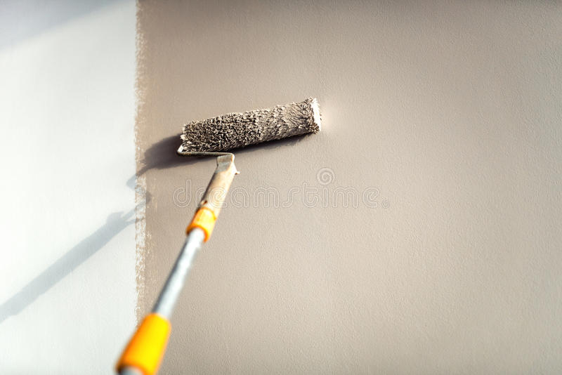 Construction worker painting walls using paint roller. stock image