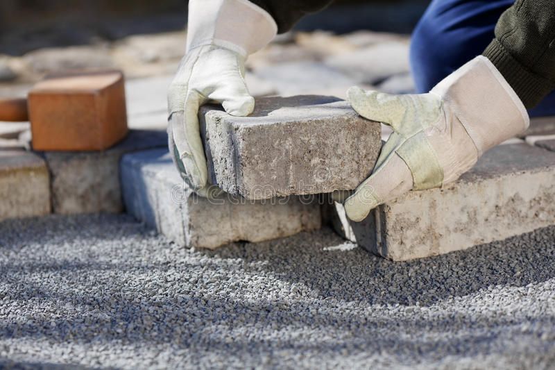 Construction worker paving the brick road stock images