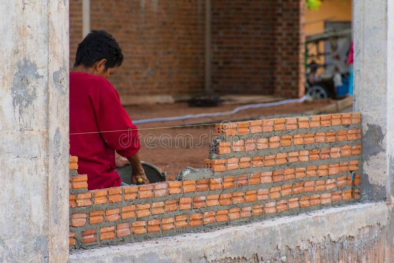 Construction worker placing bricks on cement for building exterior. Walls royalty free stock photo