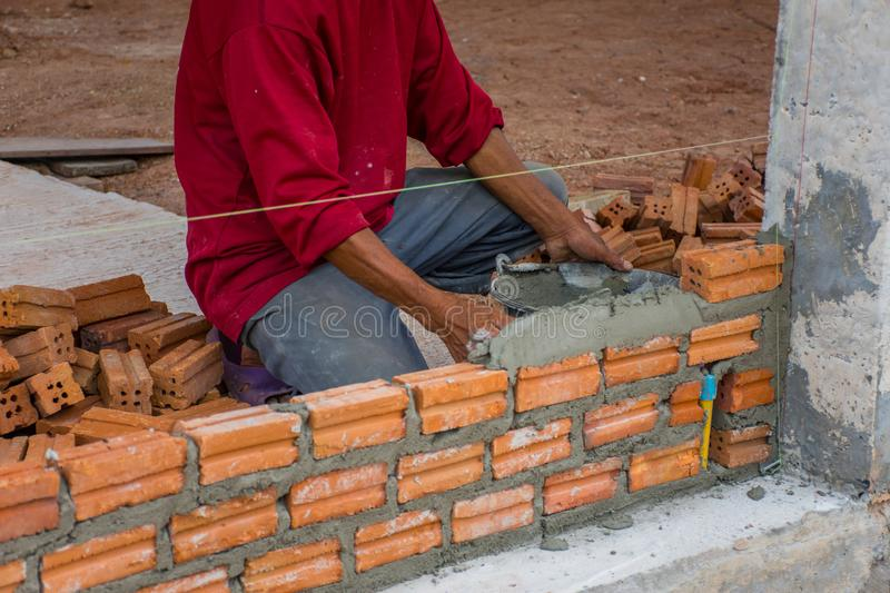 Construction worker placing bricks on cement for building stock photography