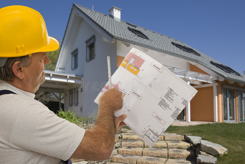 Construction worker with plan of an architect. For the planning of a house stock image
