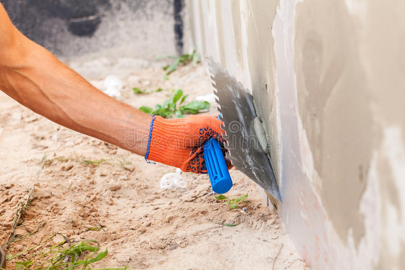 Construction worker plastering a wall and house foundation with trowel. stock image