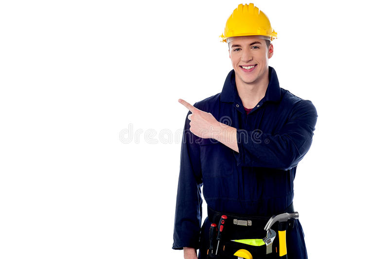 Construction worker pointing away. Young construction worker pointing copyspace area royalty free stock image