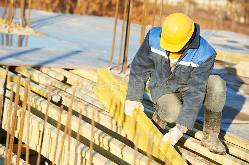 Construction worker preparing formwork. Construction worker at construction site assembling falsework for concrete pouring royalty free stock images