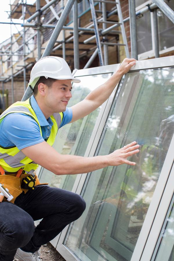 Construction Worker Preparing To Fit New Windows royalty free stock image