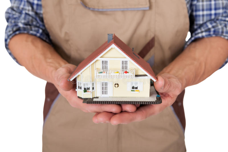 Construction worker presenting house model stock photography