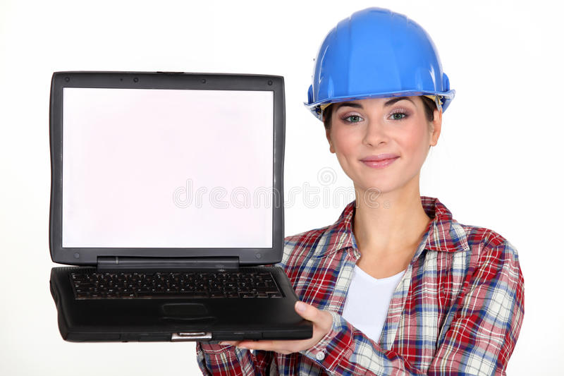 Construction worker presenting a laptop. stock images