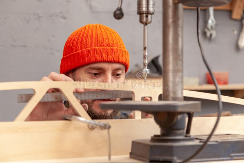 Construction Worker. Profesional drilling wood on vertical drill machine. Close up of a metal drill making holes in the wood stock photography
