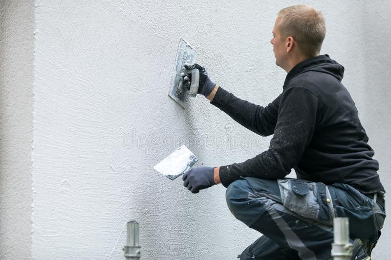 Construction worker putting decorative plaster on house exterior stock image