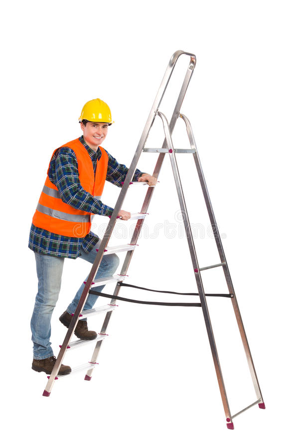 Construction worker in reflective clothing climbing a ladder. Smiling construction worker in yellow helmet and orange reflective waistcoat climbing a ladder royalty free stock photo