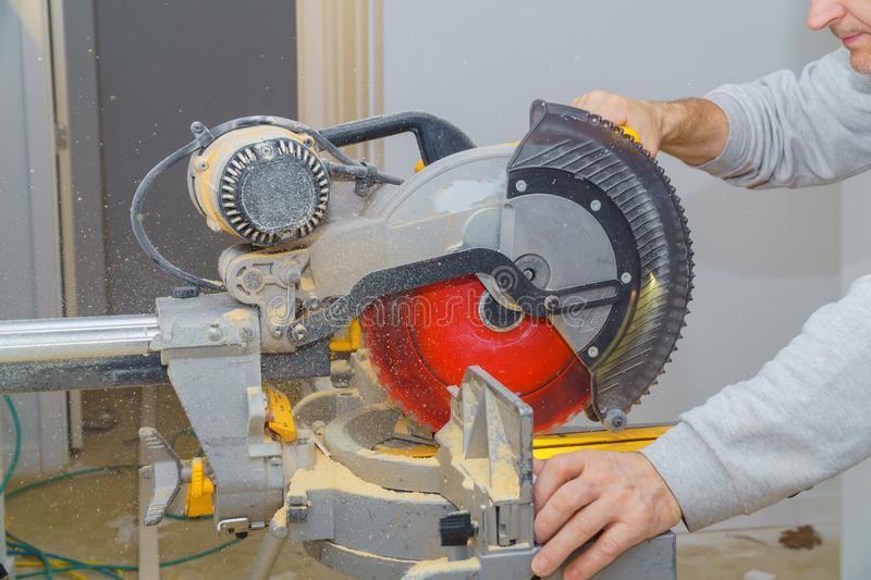 Construction worker remodeling home Carpenter cutting wooden trim board on with circular saw. Carpenter cutting wooden trim board on with circular saw royalty free stock photography