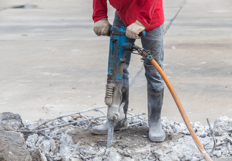 Construction worker removes excess concrete with drilling machin. E in construction site royalty free stock photography