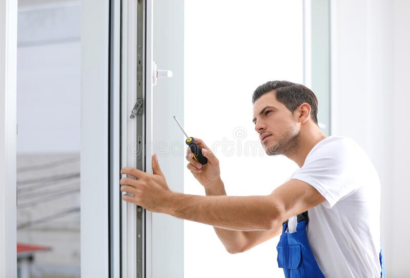 Construction worker repairing plastic window with screwdriver stock image