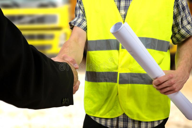 Construction worker's hand holding project documents and shaking hands. Close up of a construction worker's hand holding project documents and shaking hands stock photography
