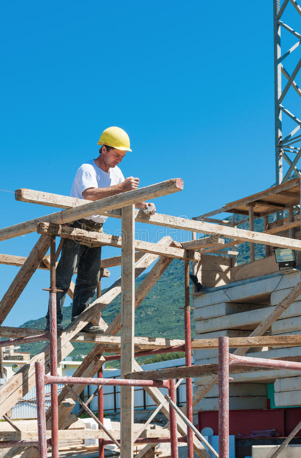 Construction worker on scaffold. Busy with guiding strings stock images