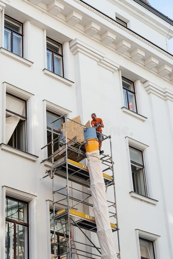 Construction worker on scaffold in building. Vienna, Austria - August 17, 2017: Construction worker on scaffold in building in Vienna stock images