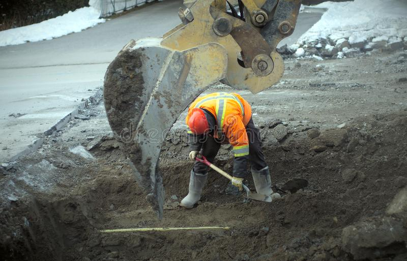 Construction worker shovel road repair drain sewer work excavation digger royalty free stock photo