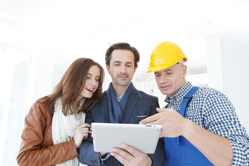 Worker and couple look at tablet royalty free stock image