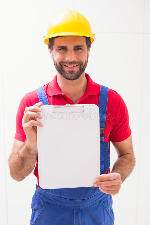 Construction worker showing clipboard to camera. In a new house stock images