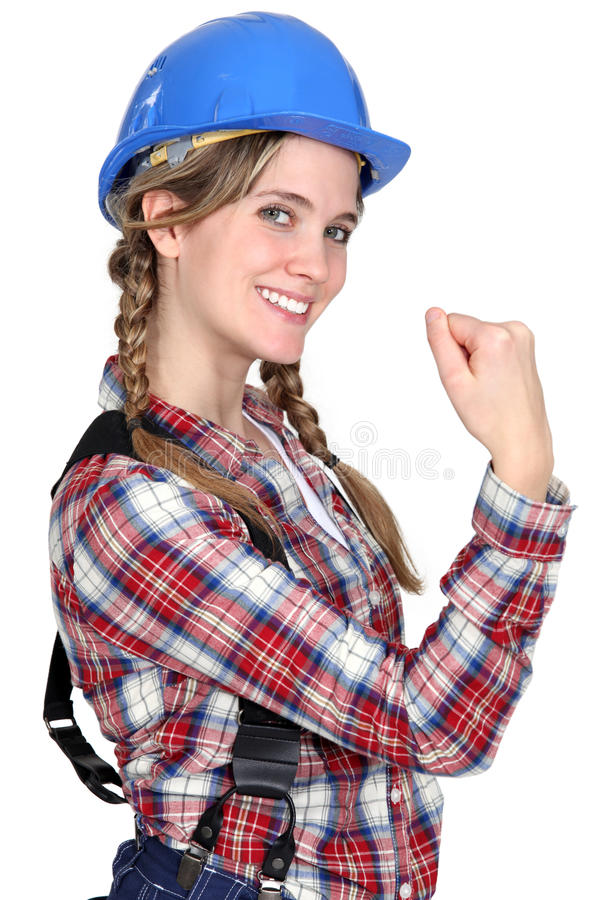Construction worker showing her strength. Female construction worker showing her strength stock image