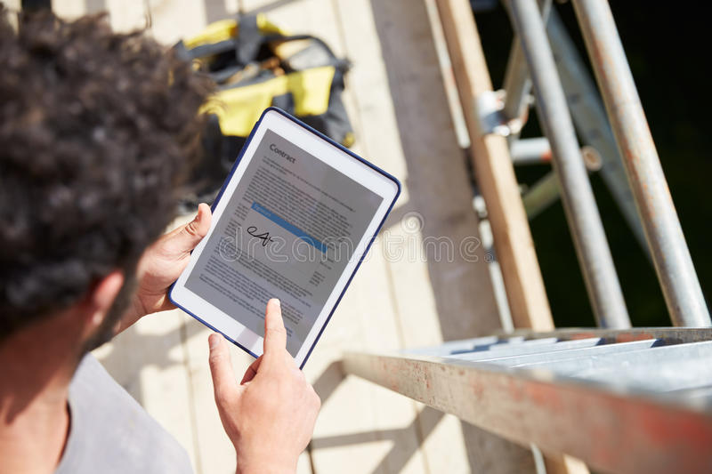 Construction Worker Signing Contract On Digital Tablet royalty free stock photo