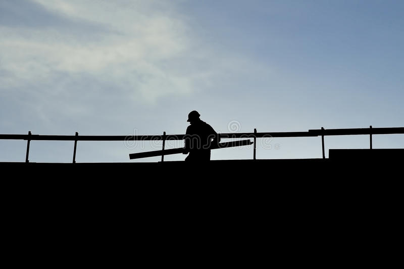 Construction worker silhouette. On a construction with blue sky on background royalty free stock photo