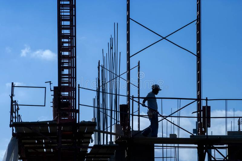 Construction worker silhouette with framing and rebar. Against blue sky royalty free stock photography
