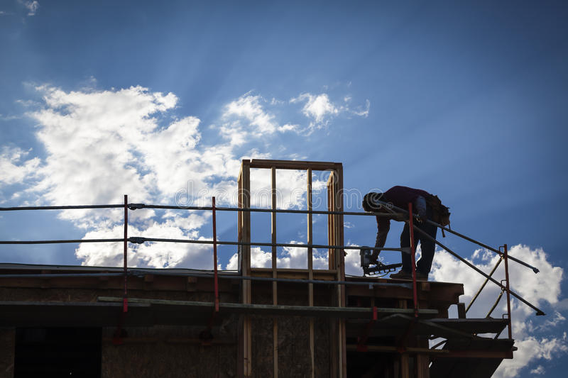 Construction Worker Silhouette on Roof. Of Building stock images